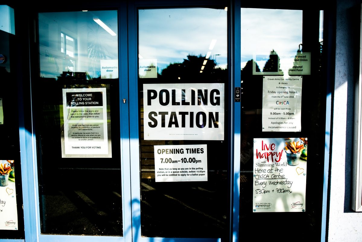 The glass doors to a building being used as a polling station.