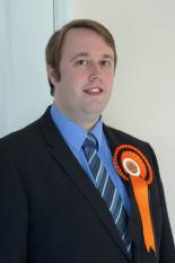 A head and shoulders photograph of Mr Knight wearing his orange election rosette.